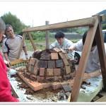 ドーム型の窯にレンガを積む