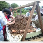 ドーム型の窯を土で覆う作業